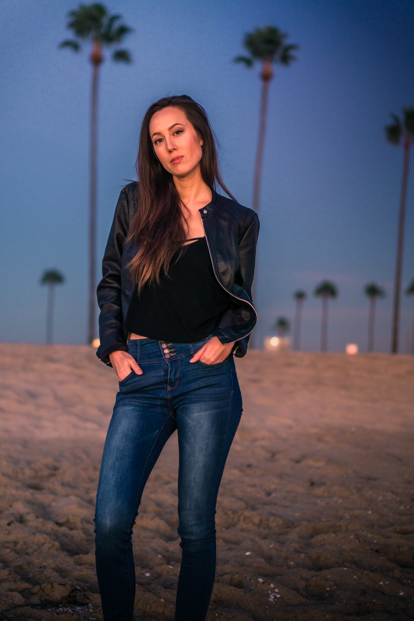 Natural light Fashion photoshoot of model posing in black leather jacket and blue jeans with blue sky and palm trees during Golden hour At Balboa Pier in Newport Beach