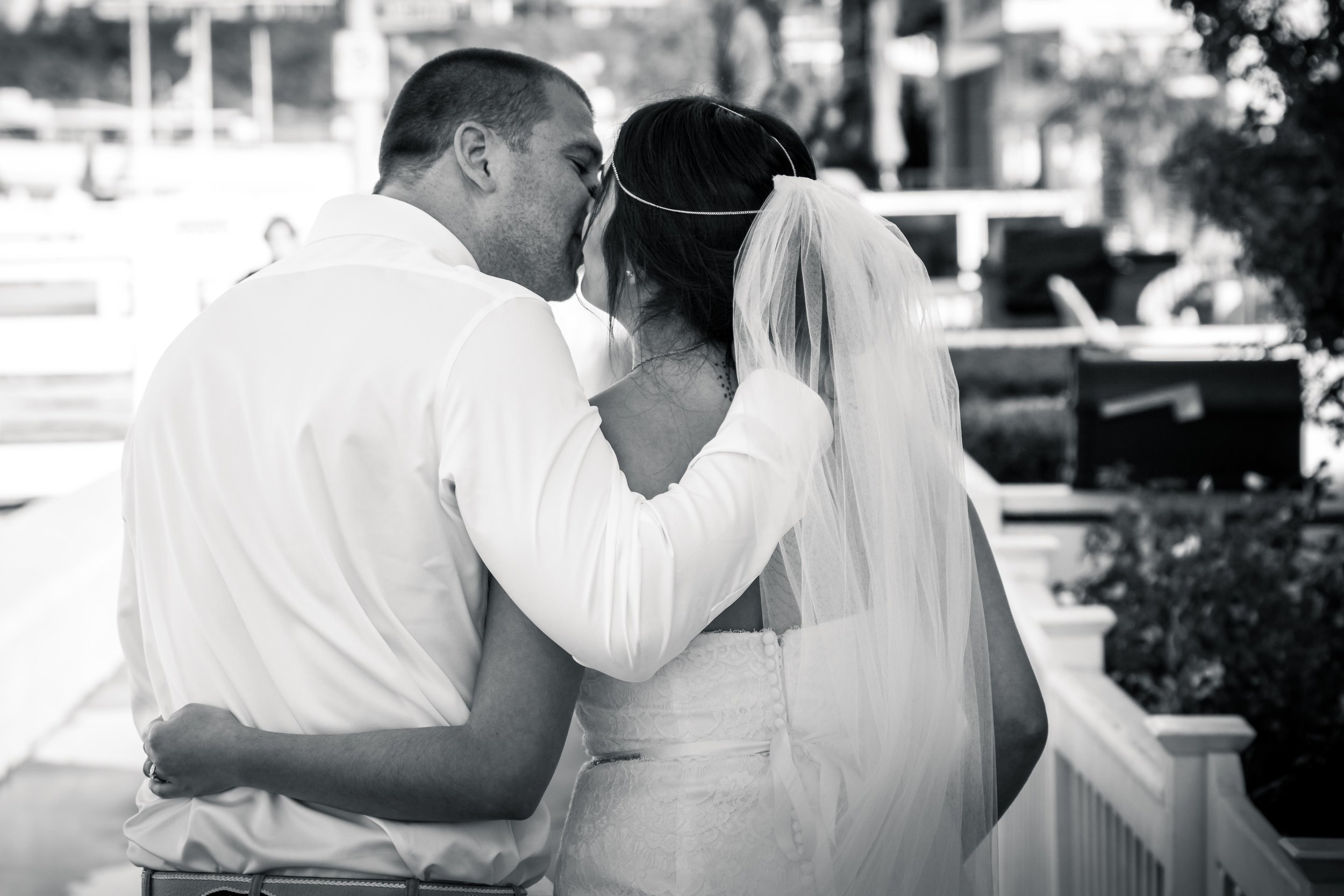 Black-and-white candid photo of the bride and groom kissing and walking together