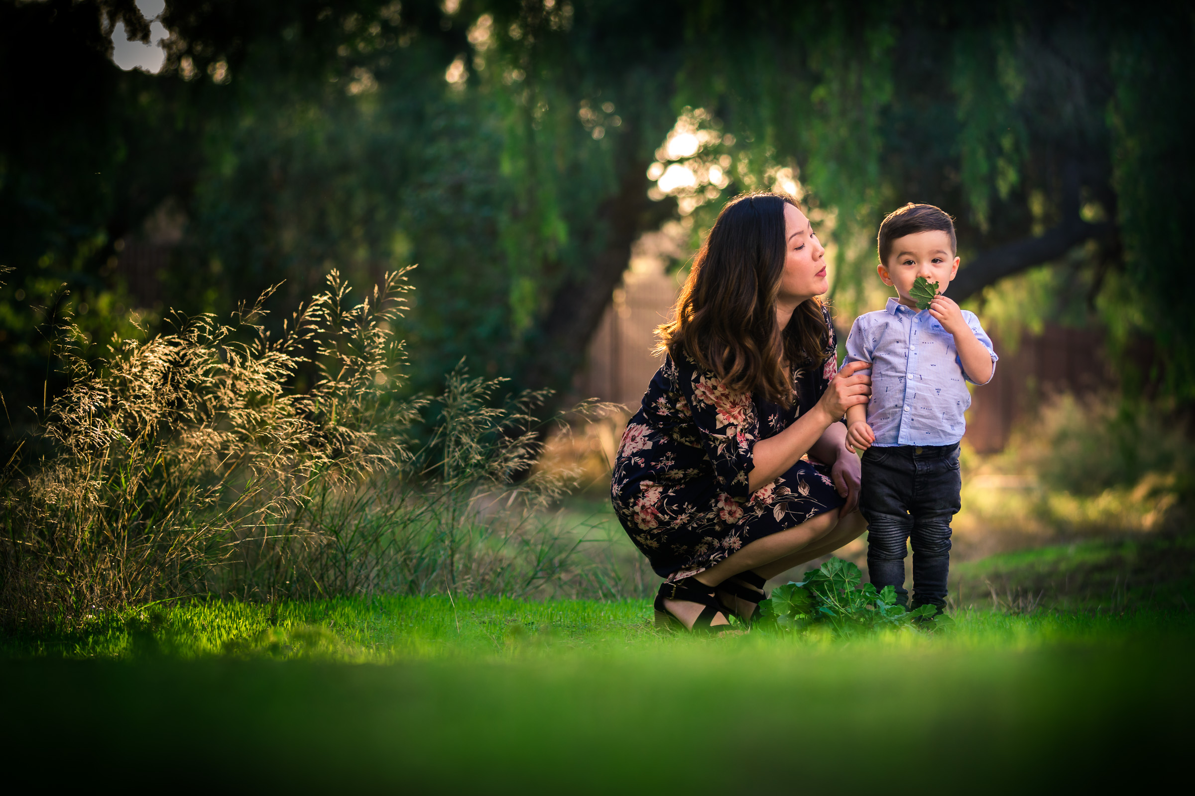 Candid photo of a little boy playing with mother during a Family portrait photo shoot in Fullerton on the Juanita Cooke greenbelt and Trail with vibrant green trees and grass and the golden hour sun