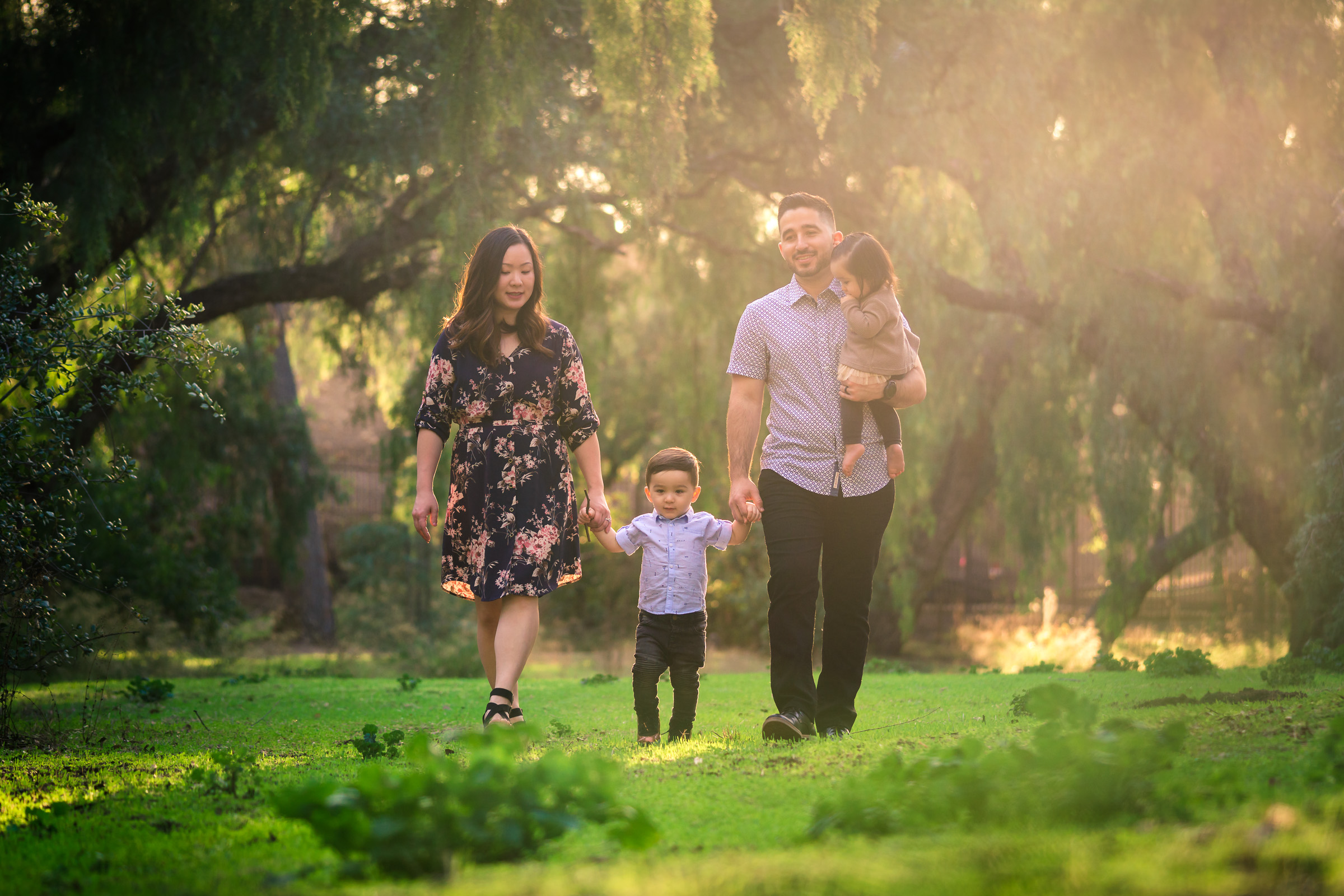 Candid photo of family walking during a Family portrait photo shoot in Fullerton on the Juanita Cooke Trail with vibrant green trees and grass and the golden hour sun