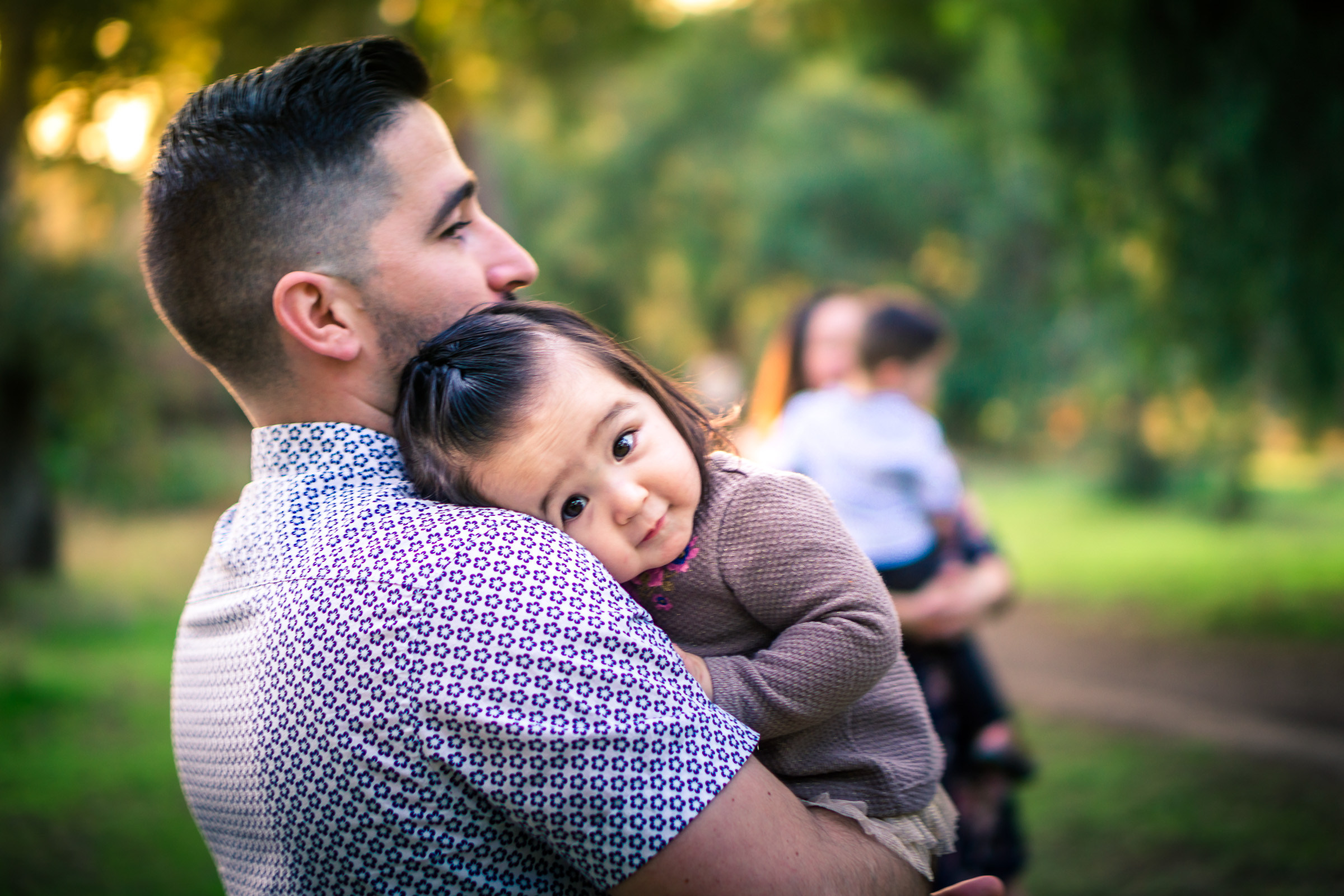 Portrait of a father holding his cute little baby girl on his shoulder during a family portrait session in fullerton orange county taken by joseph barber photography