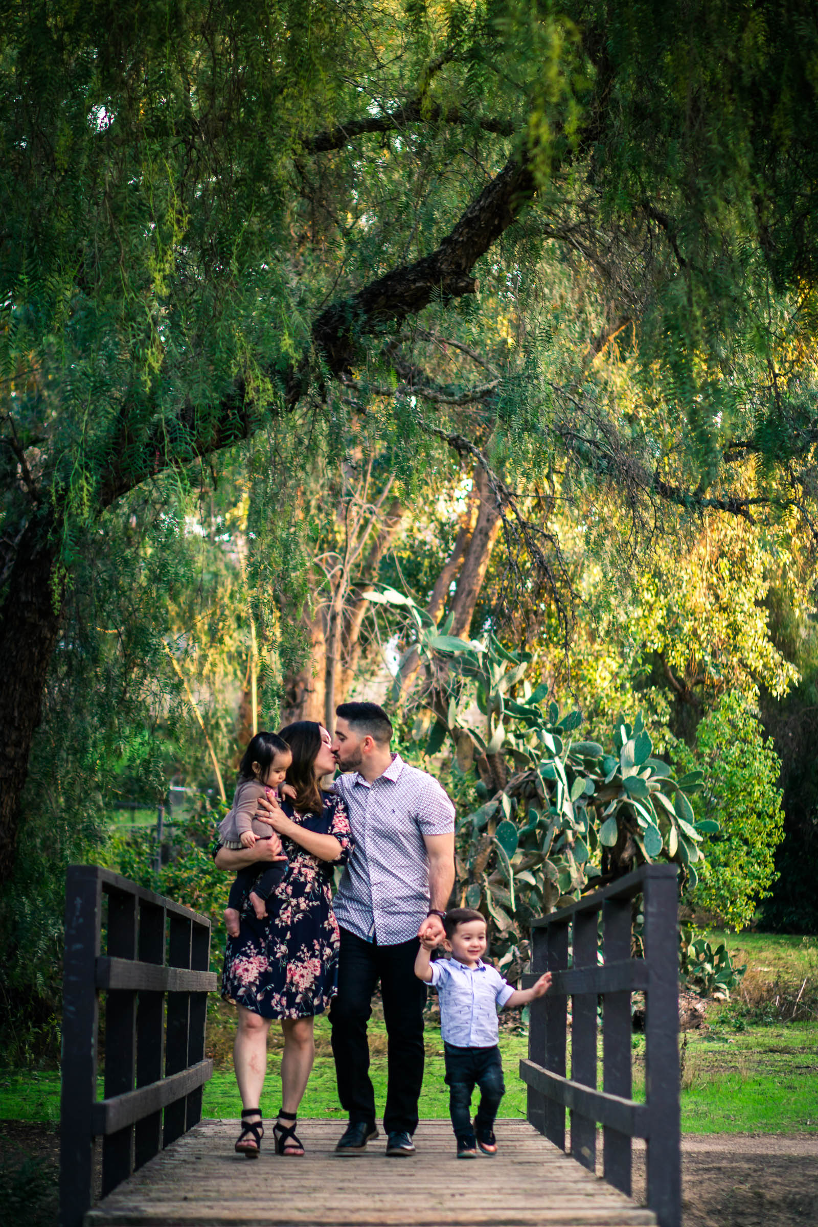 photo of a family walking across a bridge through a park during a family portrait session  on the juanita cooke trail in fullerton orange county taken by joseph barber photography