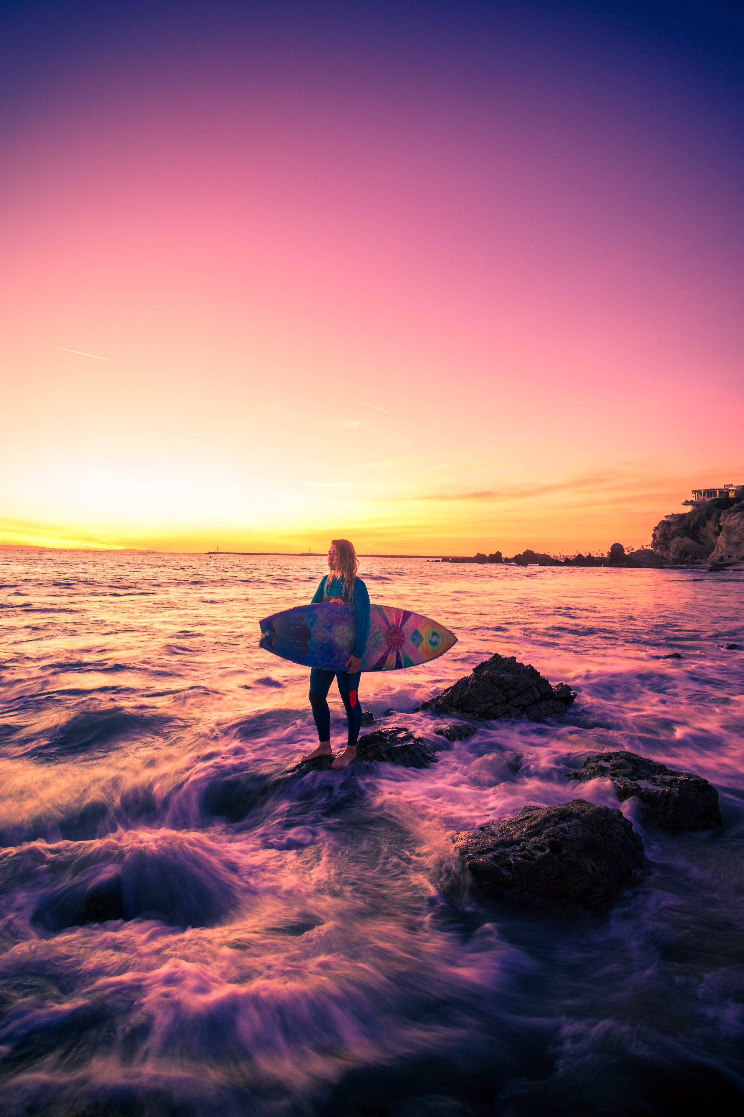 A wide-angle portrait of a surfer girl standing in the waves using long exposure techniques during a Golden and purple California sunset at little corona beach in orange county