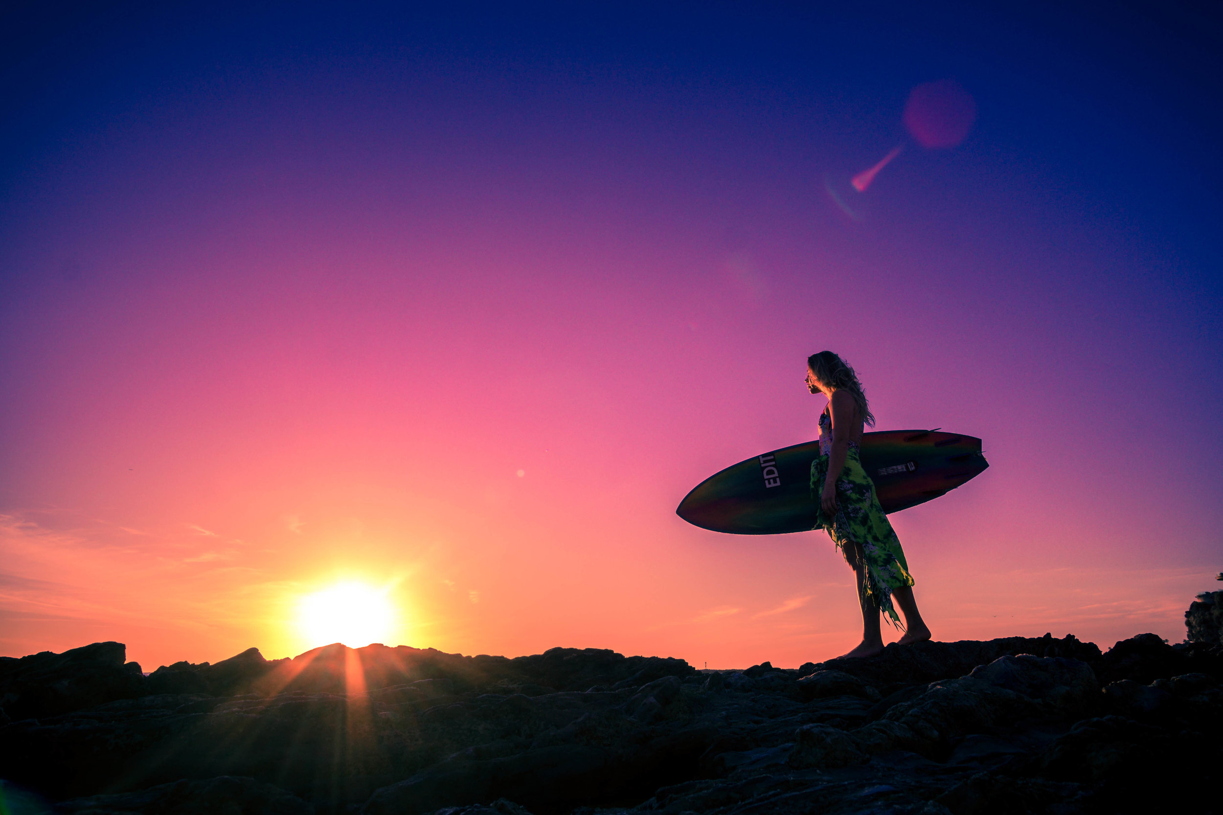 a silhouette of a surfer girl holding her surfboard on the rocks at corona Del mar beach at sunset