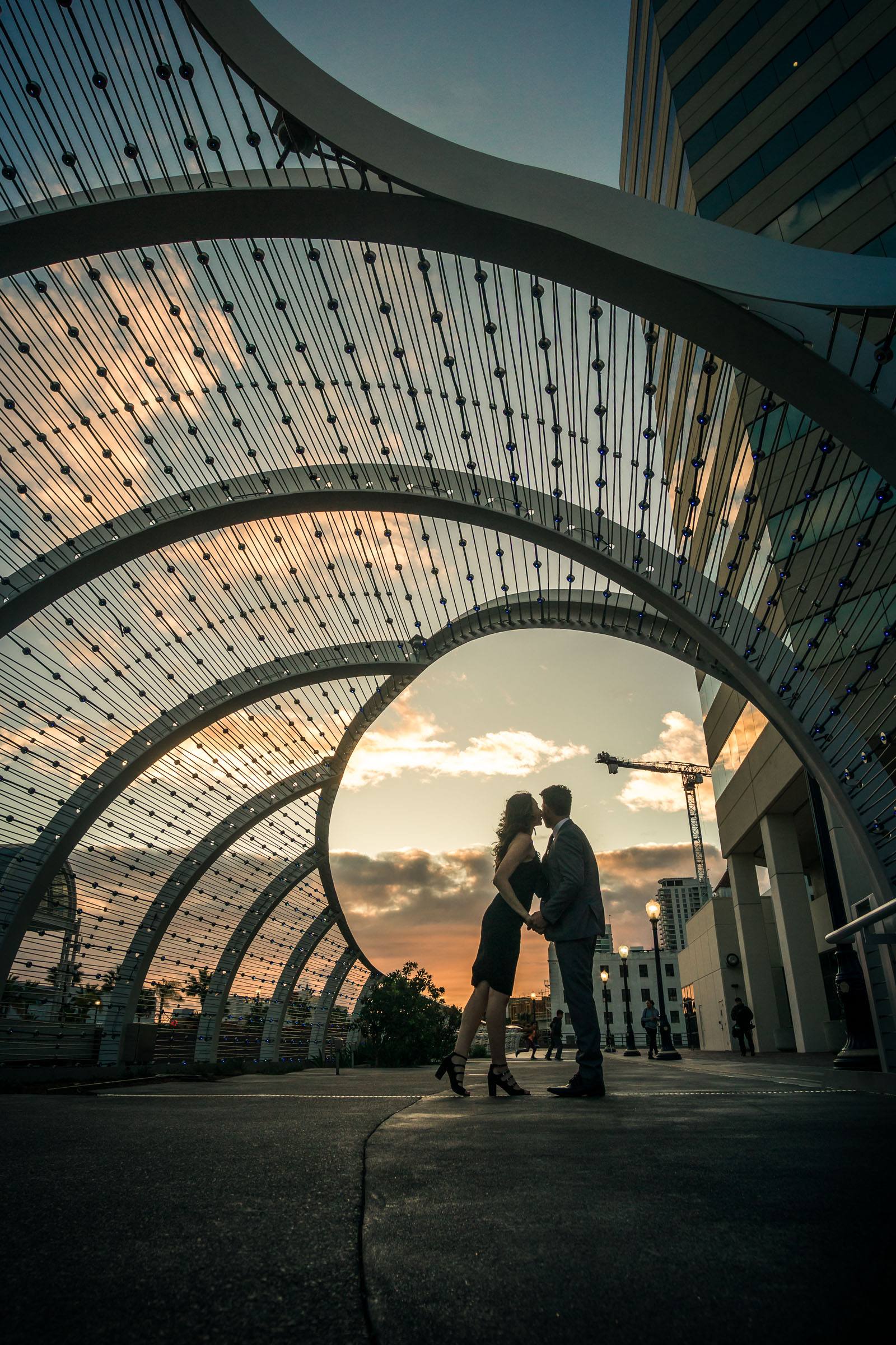 Silhouette of a husband and wife holding hands during a professional portrait photo shootat the rainbow Bridge At the Long Beach convention Center