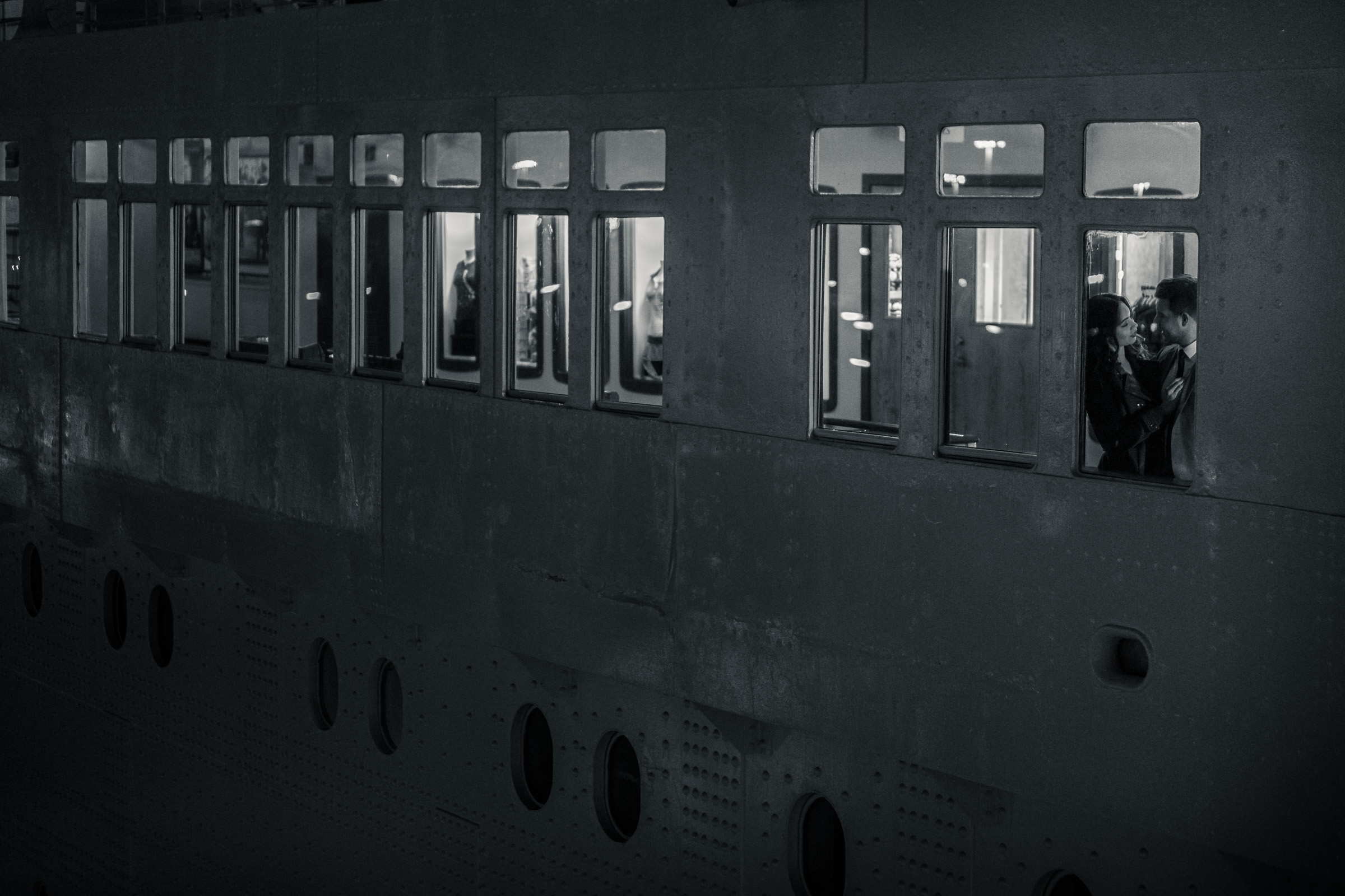 A vintage style black-and-white photo of a couple on the Queen Mary During a engagement photo shoot in downtown long beach