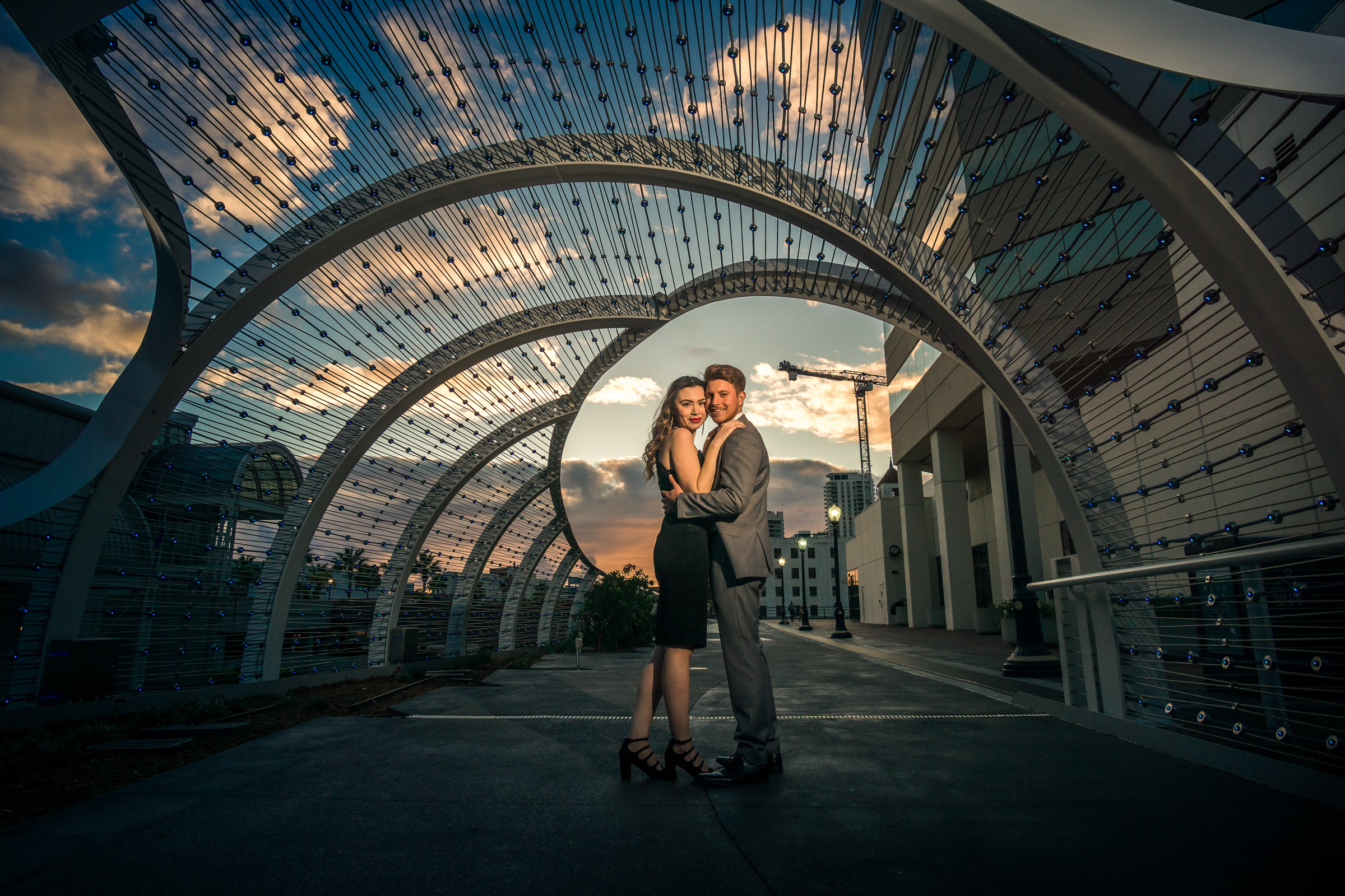 Photo taken at Golden hour of a couple under the rainbow bridge in downtown Long Beach