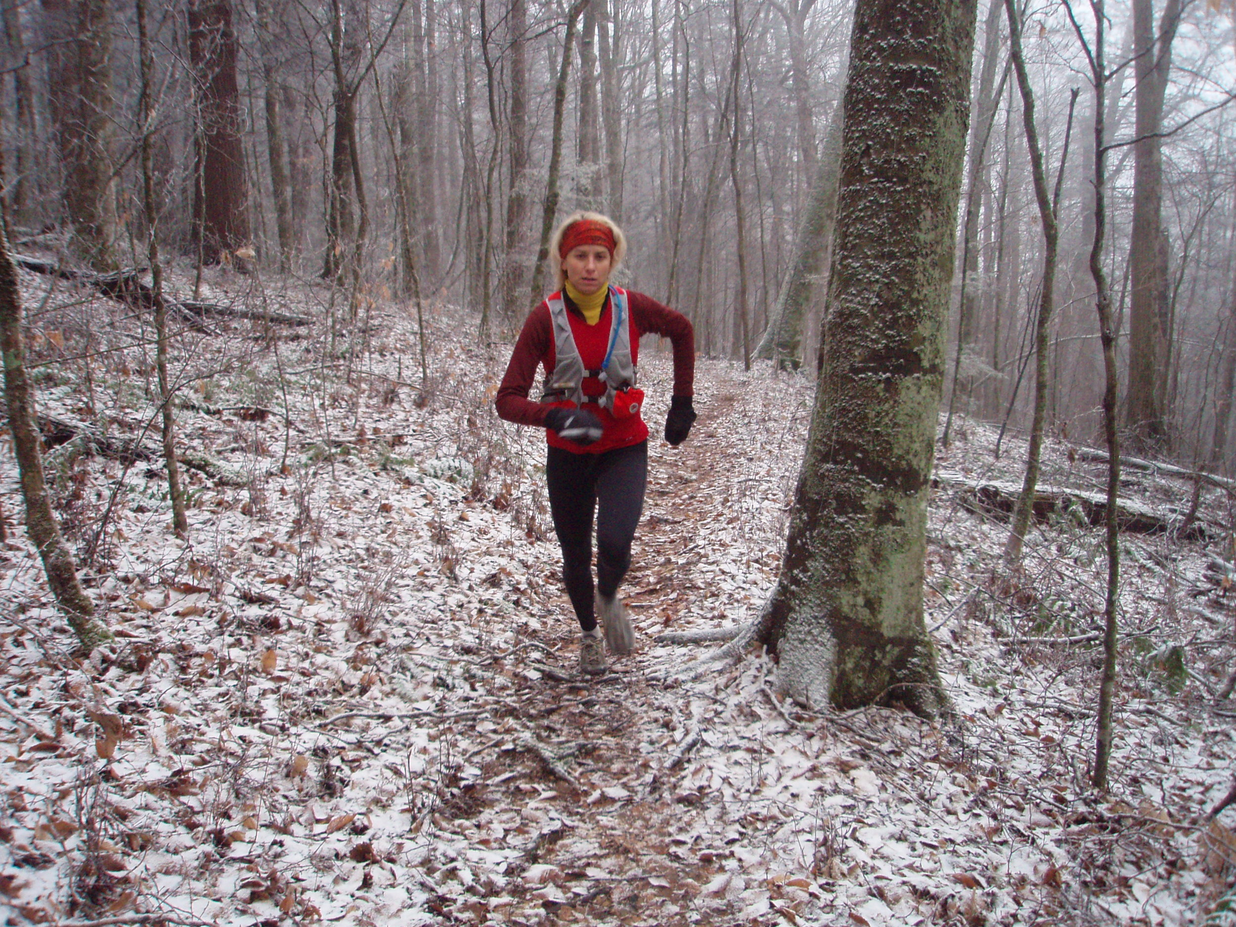 Susan Donnelly running in winter on snowy trail.