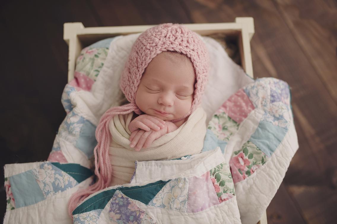 Newborn_baby_girl_In_bonnet_at_studio.jpg