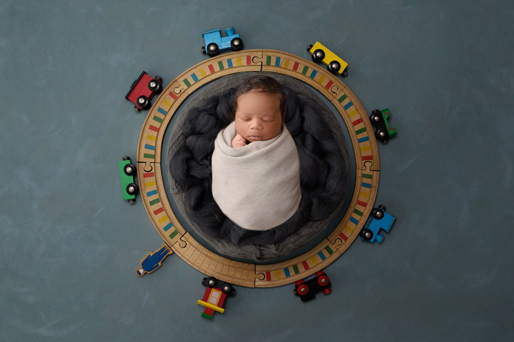 Newborn baby poses with trains at local studio in Warner Robins