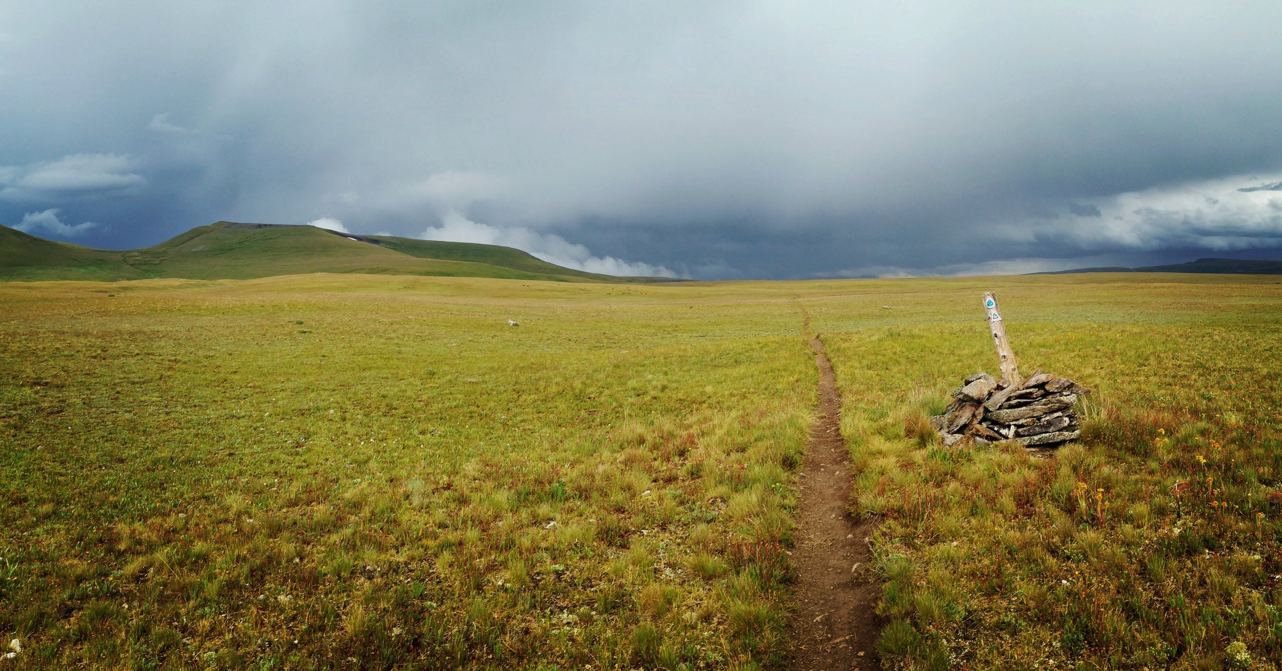 Day 26:  This shot is looking back at a terrifying storm cell that caught me exposed on top of Snow Mesa, a flat 4-mile expanse above 12,000 feet. I had to duck into a dirt washout, and hunker under an overhang of tundra grasses, to ride out the storm.  Daily mileage: 18.7. Total miles: 371.9.
