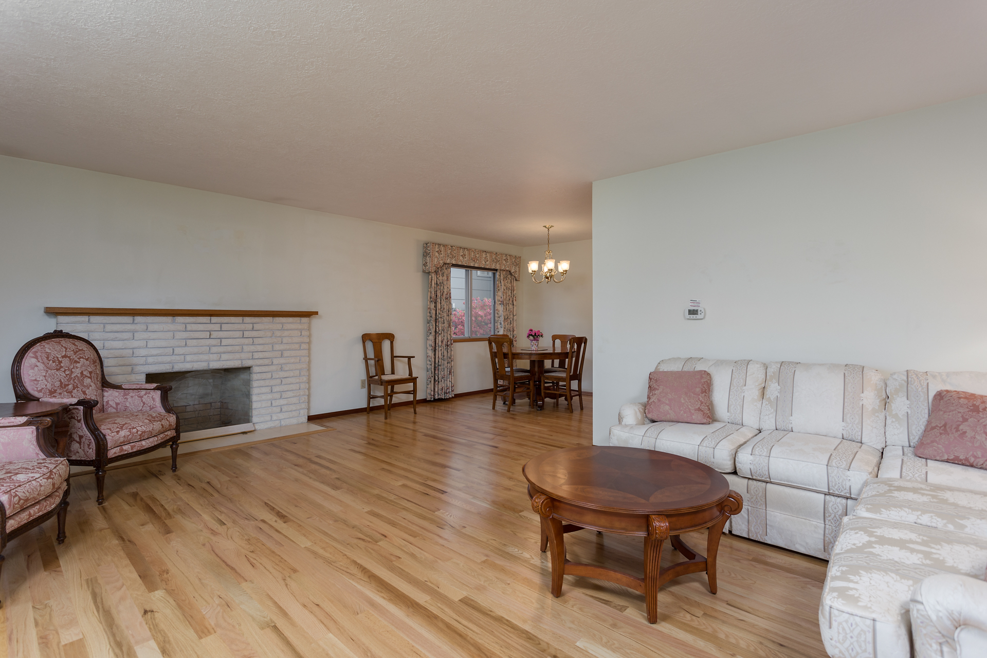 Spacious living and dining area with hardwood floors and cozy fireplace.