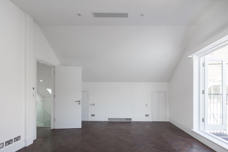 Herringbone dark flooring with stark brilliant white walls is a stunning vision.