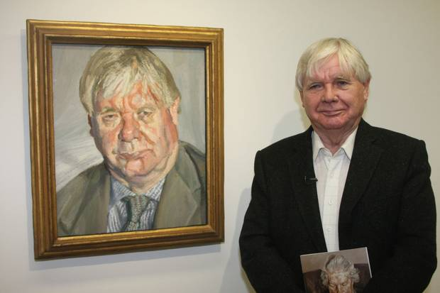 Pat Doherty standing next to a painting by Lucian Freud of himself.