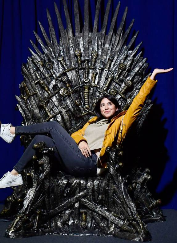 A fan poses on the Iron Throne