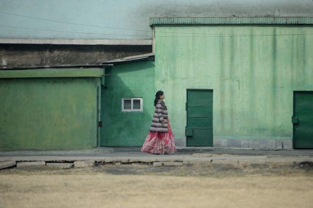 A woman wearing a traditional dress walks along a street in Pyongyang, North Korea, in March.