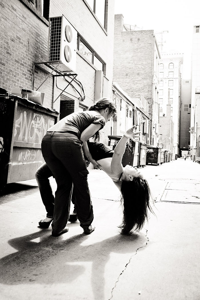 Yoga in public - blooper photo of woman helping yogi up in an alley