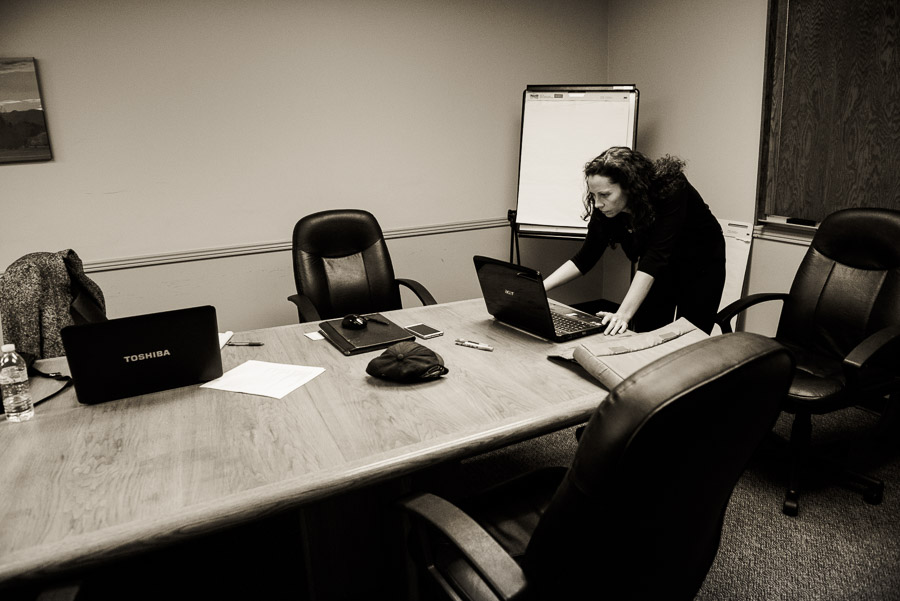 Woman alone in a conference room standing over her computer.