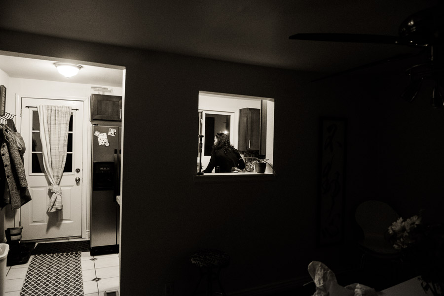 Kelly in her kitchen seen through a windwo.