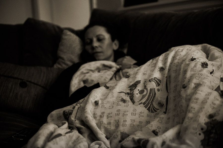 Woman asleep on her sofa under a Muppets blanket.