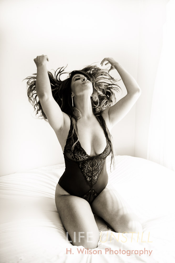 Black and white photograph of a Woman on bed in sexy black lingerie flipping her hair