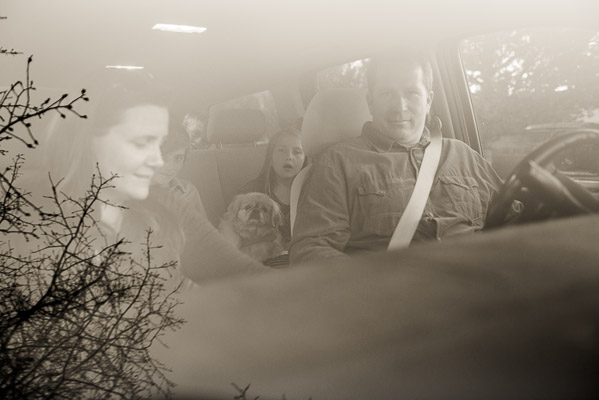 Black and white photo of famlly in their car through the front window.