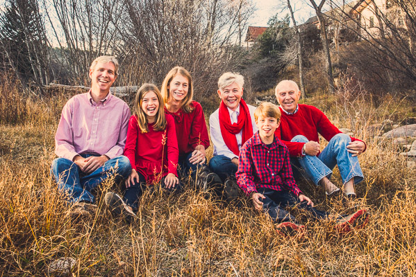 Nice family photo in the grass with grandparents parents and kids everyone dressed in red.