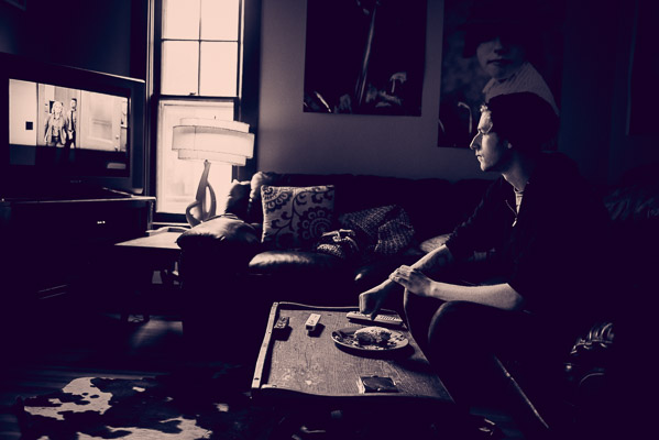 Documentary photo of young man eating and watching TV