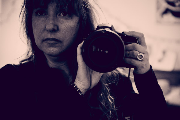 Self portrait of woman and camera in mirror.