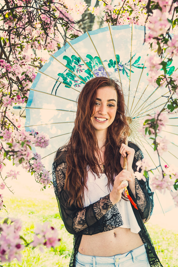 Teen girl with long red hair blowing in the wind holding a parasol with cherry blossoms in the spring.