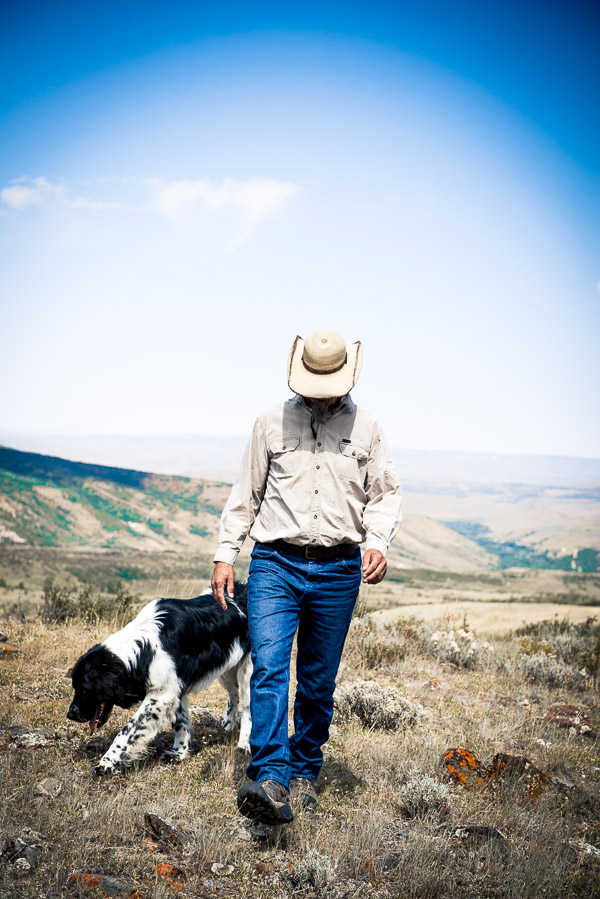 Man in a cowboy hat with a Landseer Newfoundland dog on a desert hill.