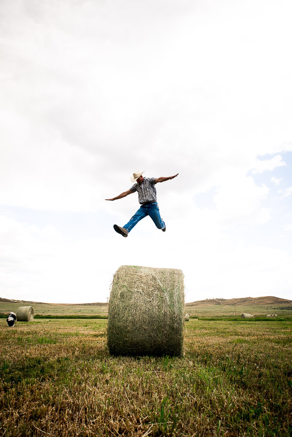 Man jumping above a hay bale.