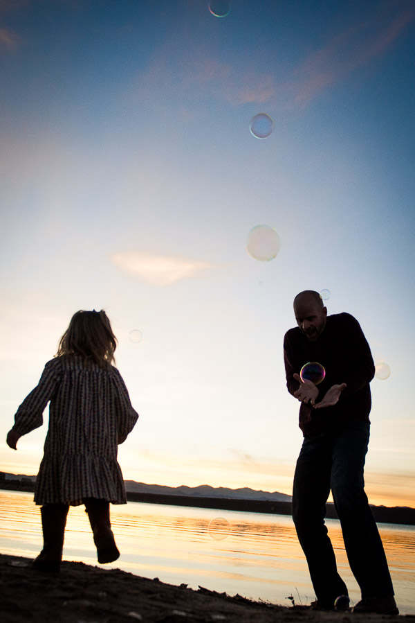 Silhouette on a beach of man catching a bubble and his daughter in the foreground.