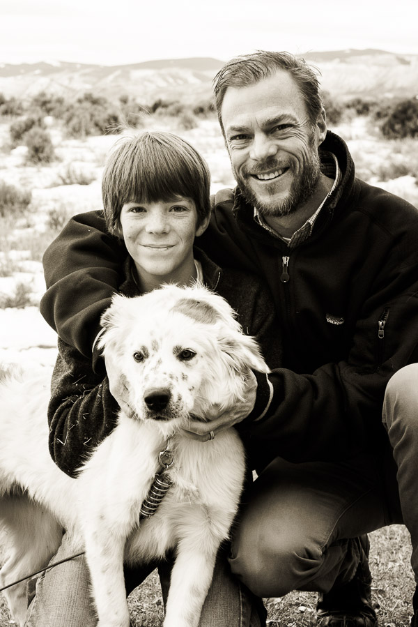 black and white posed photo of man with beard, his son, and white dog.