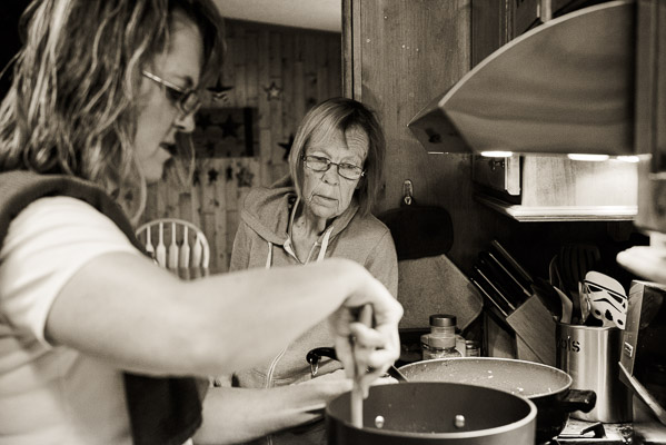 Older woman looks on as her daughter cooks.