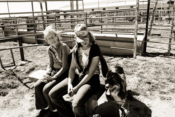 Two women sit on a benh on an ranch in the dirt.