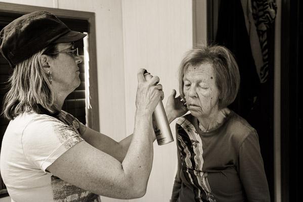 Woman spraying hair of her elderly mom.