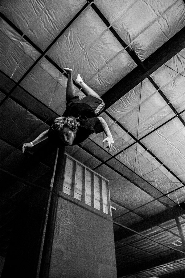 Black and white photo of white boy flipping upside down.