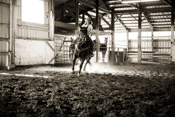 Woman galloping inside arena.