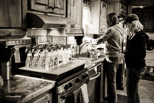Stovetop covered with empty plstic bottles while two women prepare to fill them.