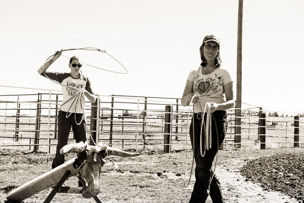 Two women by a roping dummy, one is in the middle of a toss