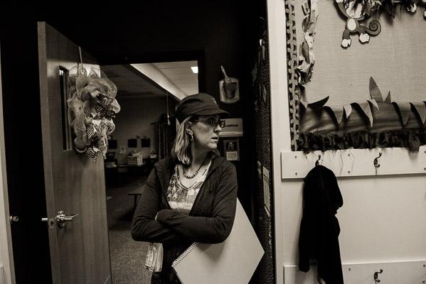 Woman waits in a hallway.