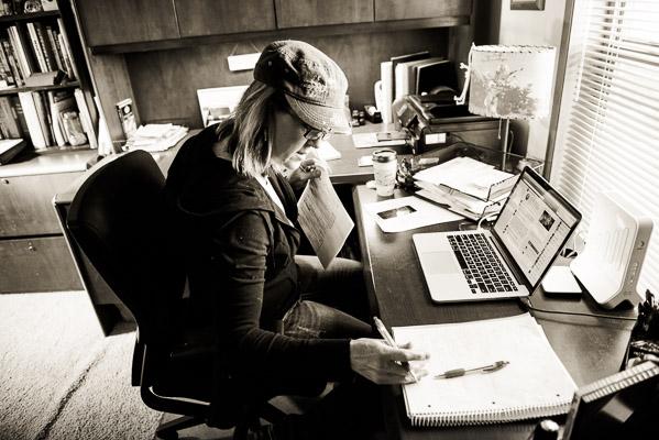 Woman doing paperwork next to an open laptop.