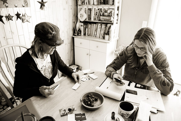 Above shot of two women working side by side at a table doing paperwork.