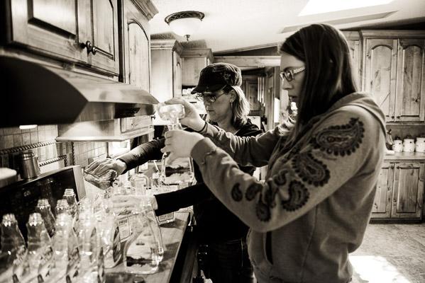 Two women filling plastic bottles in a kitchen.