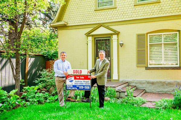 Andrew Nagel and John Sullivan in front of a sold sign.