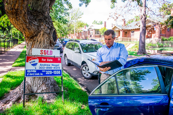 Man talks on the phone standing next to his car with a real estate sign next to him and a planner in his other hand.