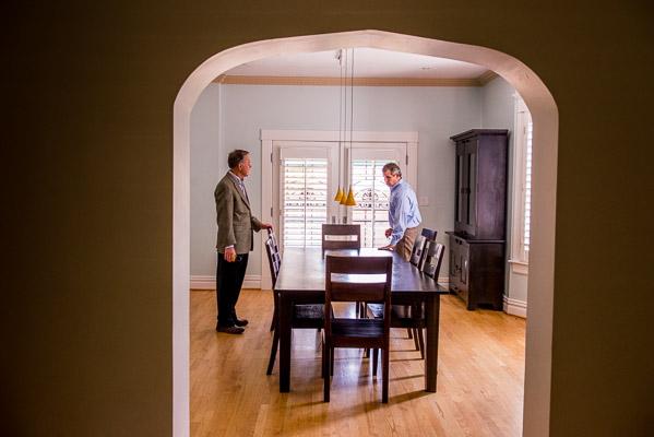 Two realtors talking inside an empty house.