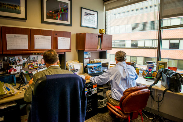 Two realtors working at their desks next to each other.
