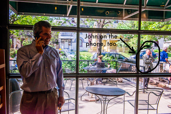 In a coffee shop, man is on the phone, outside you see another man also on the phone.